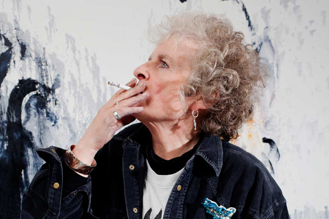 A photo of Maggi Hambling smoking in front of her painting
