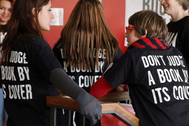 Helpers at a Human Library, wearing T-Shirts with the slogan 'Don't Judge a Book by it's Cover'