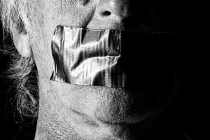 An image of a man with gaffer tape over his mouth