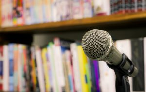 An image of an unmanned microphone in front of a row of books
