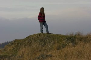 A photo of author Sara Maitland walking in the countryside