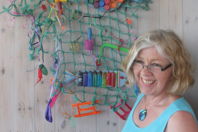 A picture of Wendy Constance in front of items found on the beach
