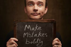 Image of storyteller and children's author Gareth P Jones holding a sign saying 'Make Mistakes Boldly'