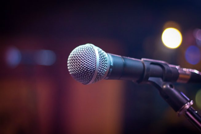 Image of a microphone in a nightclub, ready for a speaker